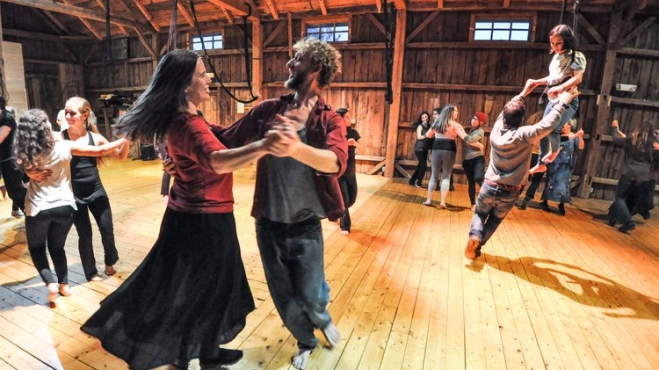 Barefoot dancing couples twirl counter-clockwise across a wooden barn.