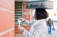 Lead project artist wears a scarf and coat while balancing a suitcase on their head. They are pouring a white, salt-like substance between two mason jars.