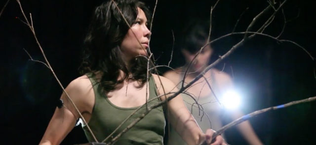 Lead project artist wears a green tank top while moving through leafless, wooden branches. Another performer is blurred in the background.