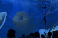 Performer on stage right is enveloped in a massive, abstract, blue projection with flower-like shapes.