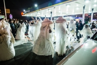 Procession of performers in giant white veils, hats, and hoop skirts within a crowded gas station at night.