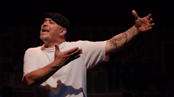 Close-up of the lead artist wearing a white t-shirt and black cap. They gesture both arms to the left as if introducing someone who isn't in the photograph.