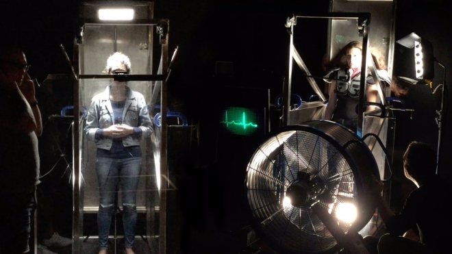 Two performers stand in glass and metal boxes with a heart monitor and a large metal fan next to them in the space.