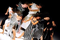 Seven dancers strongly press their arms to the right and their torsos and hair spiral to the left. They wear various combinations of white, silver, and black stripes.