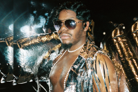 Lead project artist is surrounded by shiny mylar while wearing dark aviator sunglasses, a long sting of pearls, and a vest-like top with silver streamers.