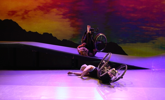 Two performers seem to be in mid-roll on their backs with their wheelchairs attached. One is elevated on a descending ramp. The ramp is lit in a lilac color, while the scrim has a rear projection of sunset colors.