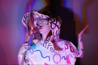 Performer wears a large maze-like headpiece and a patterned tunic with purple circles, blue squiggles, and pink triangles. They wear a mask and are holding a stick with colored ribbons.