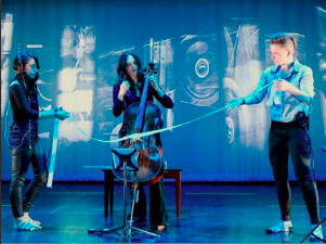 Two performers hold a long ribbon that is draped across a stringed instrument and a third performer in the middle. The stage is cast in a turquoise blue color.