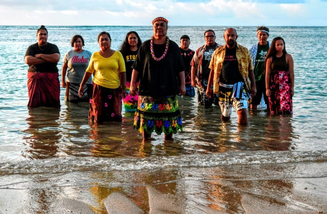 Ten people are gathered in the ocean and stand facing the shore.