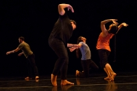 Four dancers in tanks, t-shirts, and black pants spiral in a rectangular configuration.