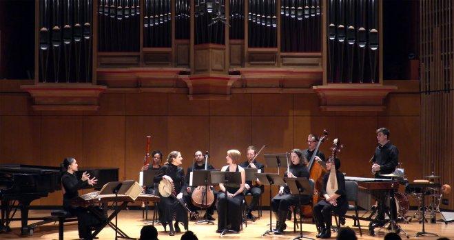 Ensemble of musicians seated beneath a massive pipe organ.