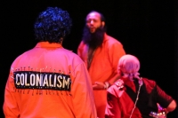 "Performer in the foreground wears an orange jumpsuit with a large black patch attached with many safety pins. ""COLONIALISM"" is printed on it in large, white, capitalized block letters. Two other performers are present in the background."