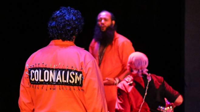 """Performer in the foreground wears an orange jumpsuit with a large black patch attached with many safety pins. """"COLONIALISM"""" is printed on it in large, white, capitalized block letters. Two other performers are present in the background."""
