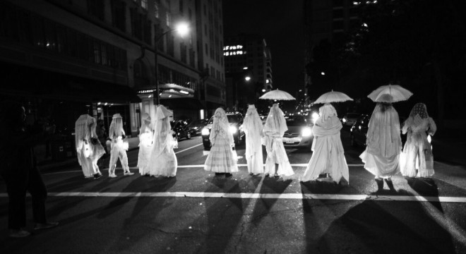 Ten performers dressed all in white with veils and umbrellas crosses a city street at night.