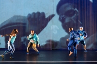 A dancing quartet travels across the stage in front of a video projection.
